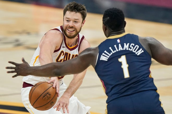 Cleveland Cavaliers' Matthew Dellavedova, left, passes against New Orleans Pelicans' Zion Williamson in the first half of an NBA basketball game, Sunday, April 11, 2021, in Cleveland. (AP Photo/Tony Dejak)