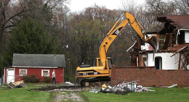 Crews tear down owner's house in front of the former Steve's Motel on Monday in Green. The demolition brings to an end a storied history that dates back to 1937 and includes the shooting deaths of Manher and Jyoti Patel, the motel's owners, and Alka, their 6-year-old daughter, in October 1991.