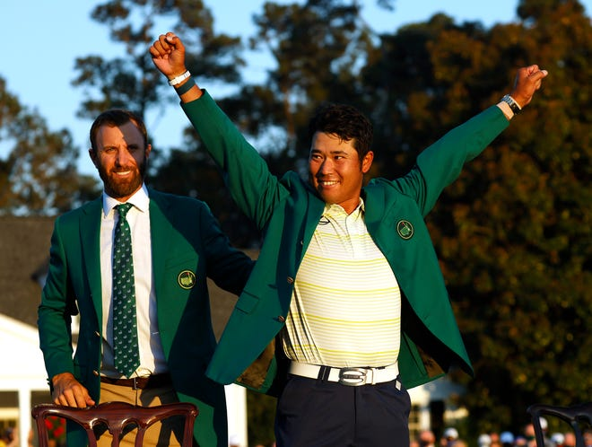 2020 Masters Champion Dustin Johnson puts the green jacket on 2021 winner Hideki Matsuyama following Sunday's final round.