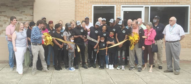 Brothers Levenski and Lamar Brown hold a ribbon cutting at the opening of their new business, L&L Sports Lounge at 210 West Broad Street in Louisville Friday, April 19. Louisville Mayor Jenny Smith welcomed the brothers and their business to the city's downtown area. Jefferson County Commission Chairman Mitchell McGraw also welcomed the brothers and their business to the area.