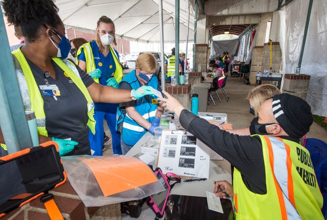 Medical personnel collect syringes and vaccination cards before vaccinating people waiting in their cars at Craig-Houghton School.