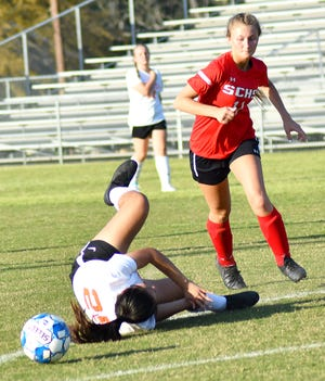 Lady Gamecock senior Lauren Brannen circles around a fallen Abigail Martinez of Metter as both soccer players battle for the ball at Kelly Memorial Stadium on April 5.
