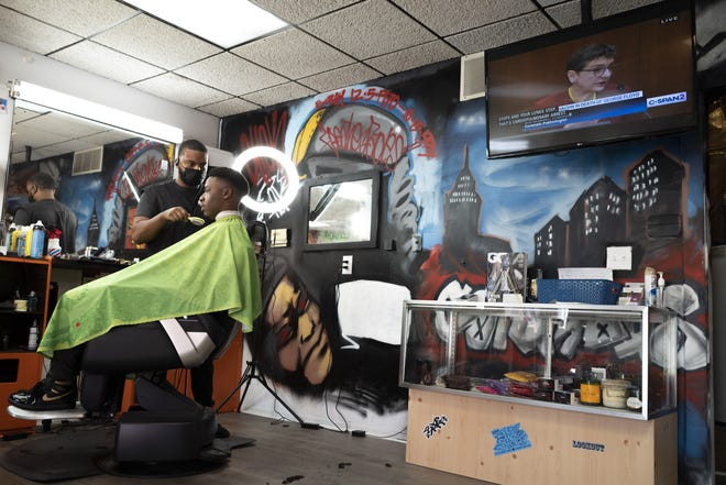 Barber Jamal Islam, left, cuts the hair of James Moore, of Pickerington, live coverage of the Derek Chauvin trial plays on the TV screen at FresherFades Barber Studio in Columbus.