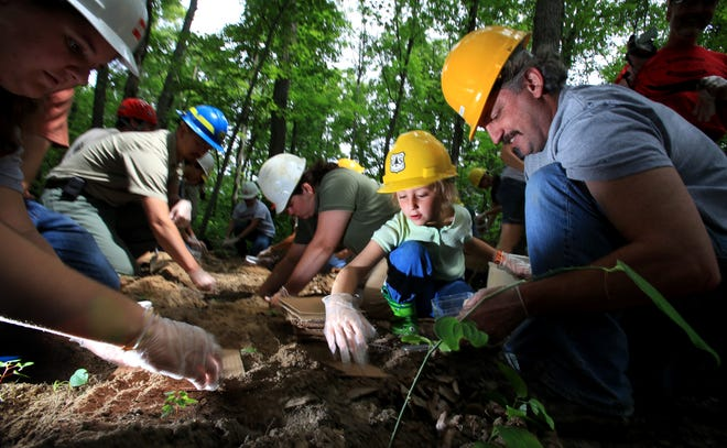 Archive photo: Olivia Blatt, 7 then, places dirt over an American burying beetle in the Wayne Forest in Perry County. Olivia was there with her father Steve Blatt (on right), a then a forest biologist with the Wayne National Forest. June 15, 2011. (Dispatch photo by Eric Albrecht)