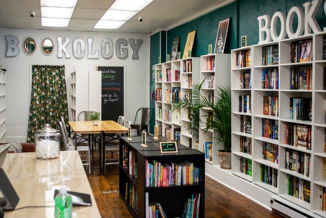 Modern tables and shelves lined with books adorn the interior of Cambridge's newest business, Bookology.