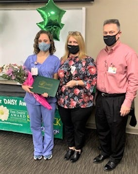 Nurse Kristi Schrock, Chief Nursing Officer Fran Lauriha and Pomerene Hospital CEO Jason Justus celebrate the DAISY Award presented to Schrock, one of two Pomerene nurses to be recognized with the award last month.