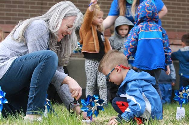 On Friday, April 9, the children of the Dodge City Community College Child Development Center, planted a blue pinwheel garden in front of the DCCC Cosmetology/CDC building to honor Child Abuse Awareness Month. Lorna Ford, DCCC Early Childhood Education Professor, helps a child position his pinwheel for the project, which is made possible by CDC staff, ECE students and CASA-Children Worth Saving Inc.