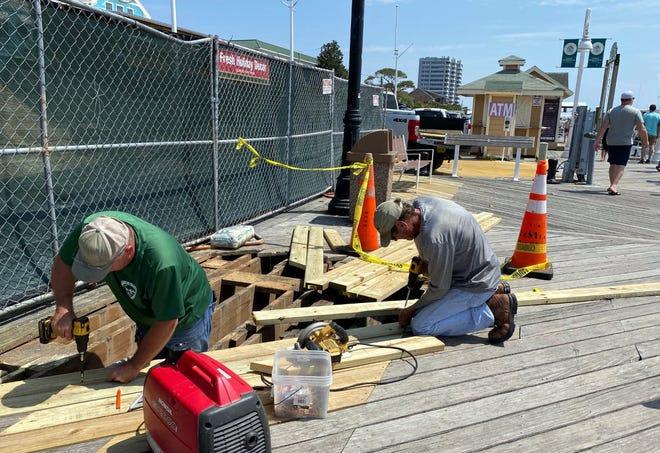 Tim Stevens and Danny Cushion work to repair the boardwalk along Destin harbor.