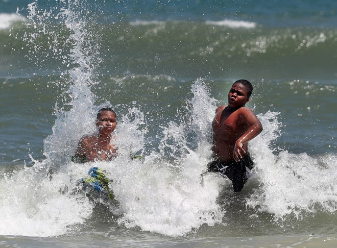 Kids play in the surf near Sun Splash Park in Daytona Beach on Monday, April 12, 2021. The area got at least 1.4 inches of rain on Sunday.