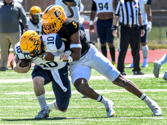 Garden City Community College defensive back Chris Smith, right, breaks through the Highland offensive line to sack Scotties' quarterback Quinn Buessing on a third down play Saturday at Broncbuster Stadium.