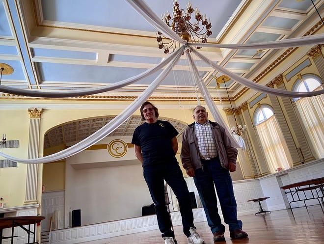 Liberal Silva, à direita, está a vender o seu edifício do Centro Cultural em Fall River ao artista Marc Dennis. Foto tirada no salão principal de banquetes do edifício.