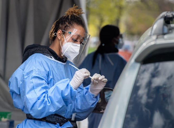 Phlebotomist Alliyah Williams explains how to use a nasal swab to a driver at the COVID-19 testing facility Friday, April 9, 2021 at the Peoria Civic Center parking lot.