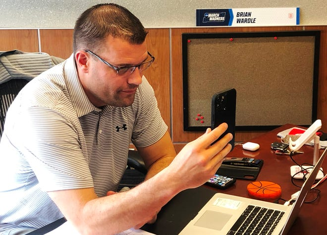 Bradley University men's basketball head coach Brian Wardle, in the midst of checking an analytics file on his laptop, takes a Facetime call from a player recruit, all in a day's work in the BU recruiting war room at Renaissance Coliseum.