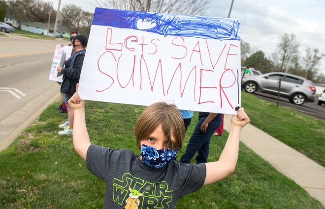 Clayton Hawkins, 9, holds up a protest sign against Peoria Public Schools' proposed year-round calendar Wednesday, April 7, 2021 outside the district office on Wisconsin in Peoria.