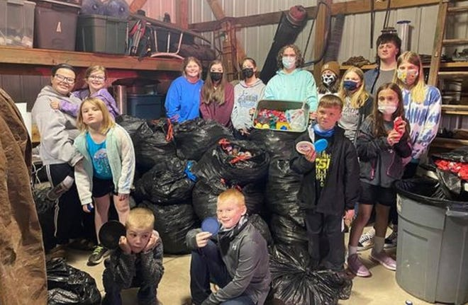 Members of the Middletown 4-Hers and Cloverbuds stop for a photo around the bags of caps they have collected in order to make benches from the caps.