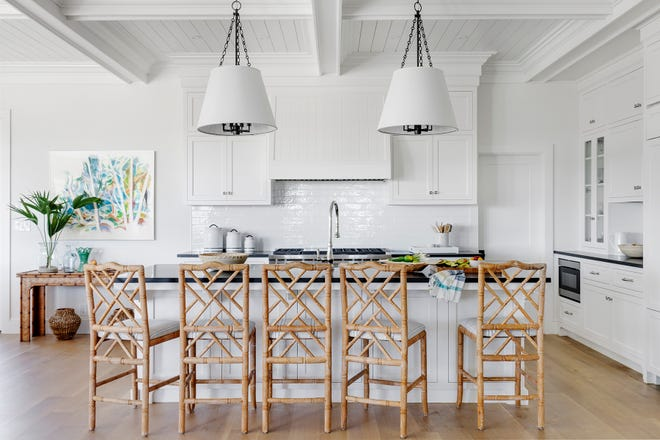 Bungalow 5 stools sidle up to the kitchen island, which is illuminated by pendants from Hudson Valley Lighting.