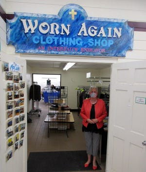 Barb Albrecht poses April 9 at the entrance to the Worn Again Clothing Shop inside Parry's General Store in Hamilton. Albrecht and all of the volunteers look forward to reopening the store June 1 for sales of spring and summer clothing.