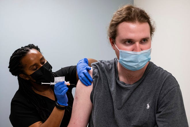 Cole Smith receives a Moderna variant vaccine shot from clinical research nurse Tigisty Girmay at Emory University's Hope Clinic, on Wednesday afternoon, March 31, 2021, in Decatur, Ga. Smith, who received Moderna's original vaccine a year ago in a first-stage study, said returning wasn't a tough decision.