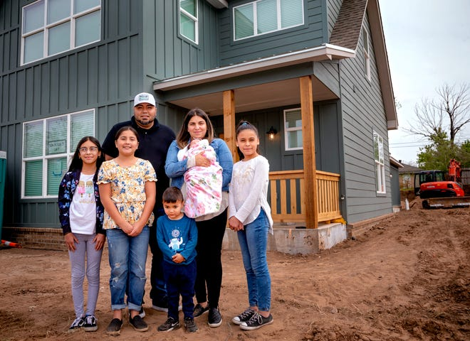 Issac and Sara Gallegos, with their children, Aracely, 12, Natalie, 9, Benjamin, 3, Gianna, 2 months, and Leslie, 11, stand outside their new home that the nonprofit ministry FaithWorks of the Inner City built in the Shidler/Wheeler neighborhood in Oklahoma City.