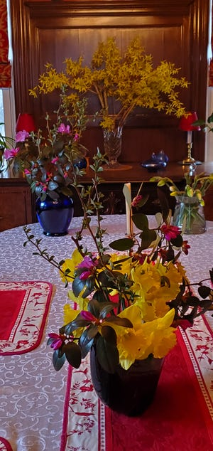 Suzette Standring enjoys the spring blooms that sit in vases on her dining room table.
