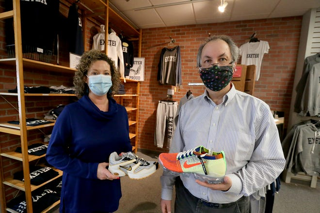 """From left, St. Vincent de Paul Executive Director Molly Zirillo holds the Nike """"Air Exeter"""" shoe made in 2000, while George & Phillips owner Bert Freedman holds the new """"Exeter Edition"""" that will be raffled off to benefit St. Vincent de Paul."""