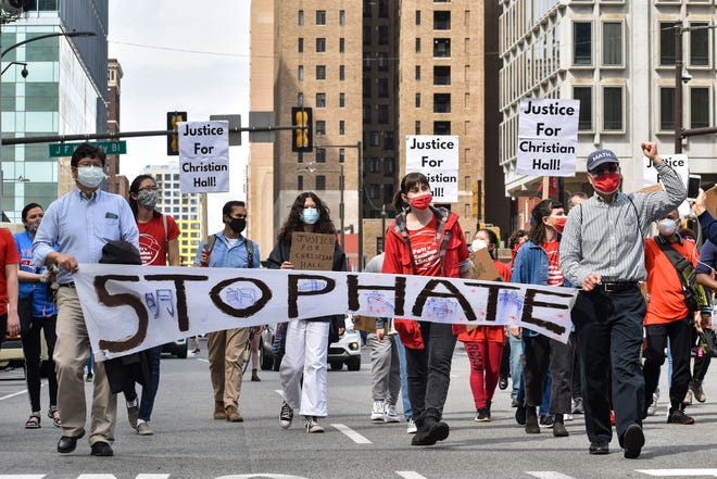 """Protesters carrying a """"STOP HATE"""" banner marchin Philadelphia on Saturday, April 10, 2021."""