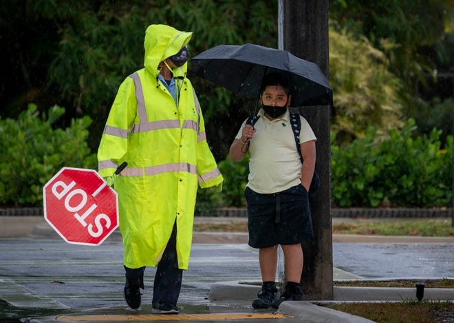 A crossing guard helps a student cross Lake Avenue in the rain next to Belvedere Elementary School in West Palm Beach, Florida on April 12, 2021. GREG LOVETT/PALM BEACH POST