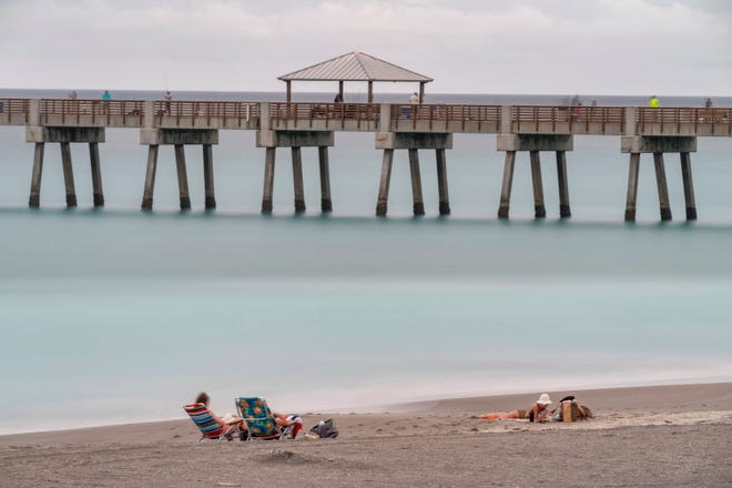 Beachgoers lounge near the Juno Beach Pier in Juno Beach, Florida on April 12, 2021. A 30 second time exposure makes the water appear flat.