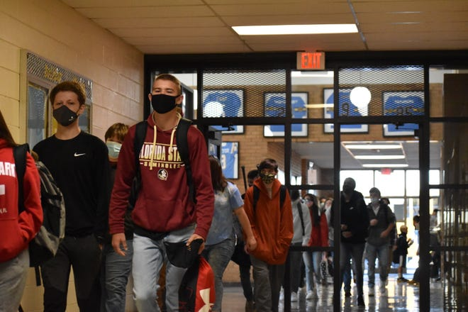 Students file in from the bus lot at Burns High School on Monday.