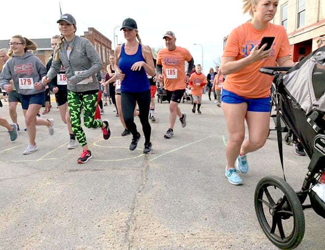 Runners in a 5K to support the foster-care group Rooted, begin their sprint Saturday in downtown Burr Oak.