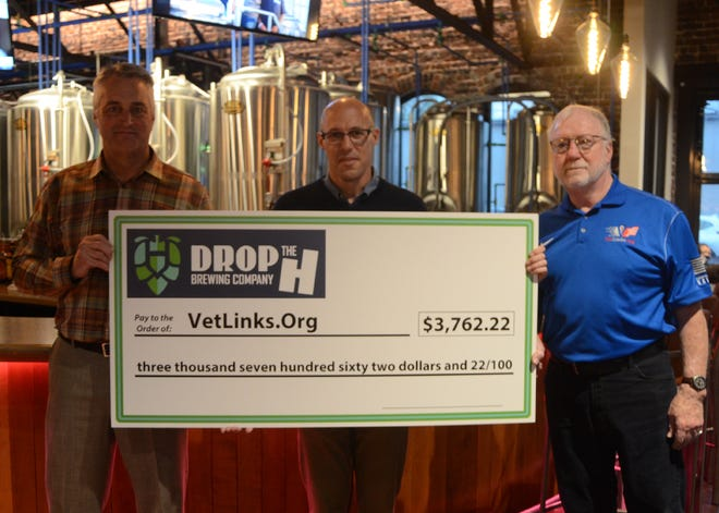 Drop The H co-owner Mark McClain, left, presented a check on Friday to VetLinks board member Joe Fleming, center, and Dennis Kavanagh, father of U.S. Army Maj. Brian Kavanagh.