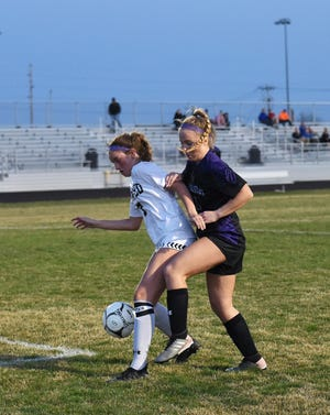 Central Iowa United's Brooke Christie tries to fend off Nevada's Chloe Henry as she controls the ball during the first half of CIU's 4-1 loss to the Cubs in its season opener April 5 at Cub Stadium in Nevada.