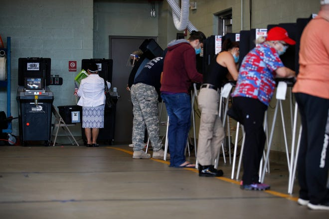 Voters fill out their ballots inside a polling place in Miami Beach on Nov. 3.