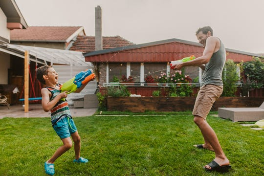 A father and son have a water fight in the yard.