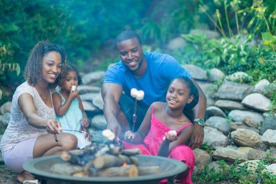 A family roast marshmallows over a camp fire.