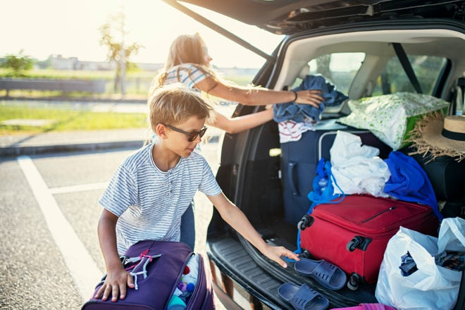 Kids help pack the family car for a road trip.