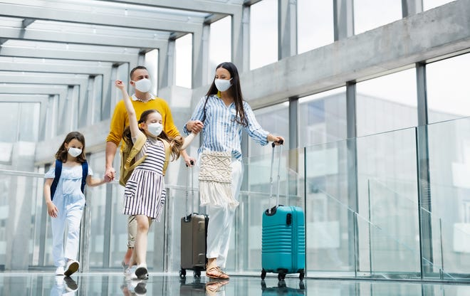 A family walks through an airport while wearing masks to adhere to Covid-19 safety protocols.