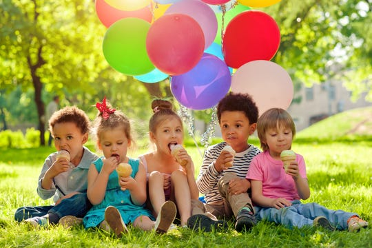 Children with colorful balloons eat ice-cream in the park