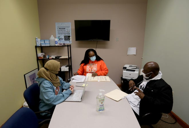 (L to R) Farhana Akter, 27 of Hamtramck, Remeta Hicks-Montgomery, 36 of Detroit, of Detroit Action talk with Antrone Richardson, 47 of Detroit and get information from him to fill out an application for a new birth record in their offices in Detroit on Tuesday, April 6, 2021. 