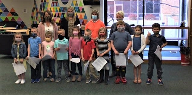 In front, left to right are first grade students at R.C. Waters Elementary School:  Rylee Wagner, Weston Hill, Quinn Guerin, Hudson Hathaway, Marley Graber, Braxton Bauer, Lorraina Reif, Cameron Pfeiffer, Payzlie Dinan, and Beckett Bryant. In back are R.C. Waters Elementary Principal Dawn Bryant, Assistant Principal Angie Lipstraw,  first grade reading teacher Cassie Dornbusch, and first grade teacher Ann Mussell.