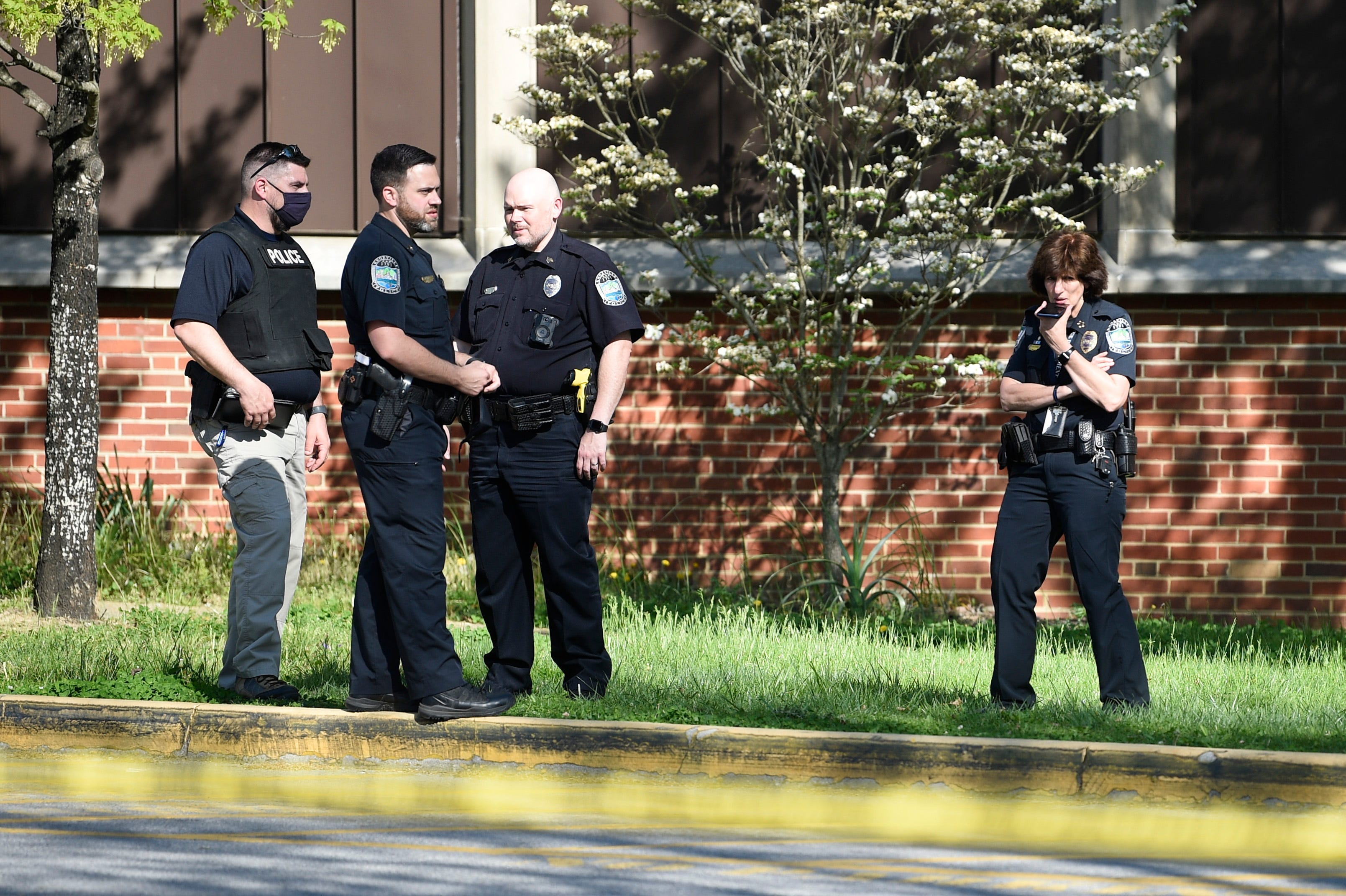 At right, Knoxville Police Chief Eve Thomas speaks on the phone outside Austin-East High School in Knoxville, Monday, April 12, 2021. Multiple people have been shot, including a Knoxville police officer, according to the Knoxville Police Department.