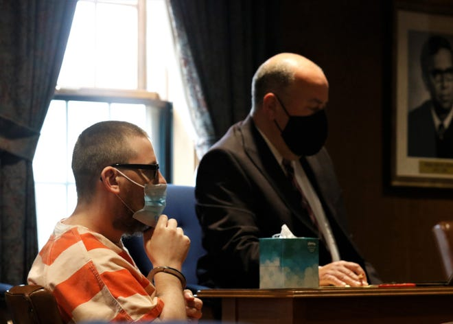 Anthony Cook, left, sits with his defense attorney Andrew Sanderson during Cook's plea and sentencing hearing Monday, April 12.  Cook was sentenced to 18 to 22.5 years in prison after pleading guilty to multiple felonies.