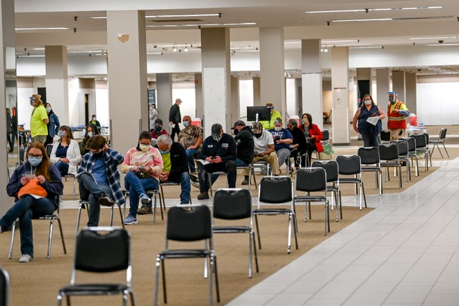 People wait 15 minutes after getting vaccinated at Sparrow's COVID-19 vaccination site in the former Frandor Sears on Monday, April 12, 2021, in Lansing. The time is to make sure people don't have any reactions to the shot.