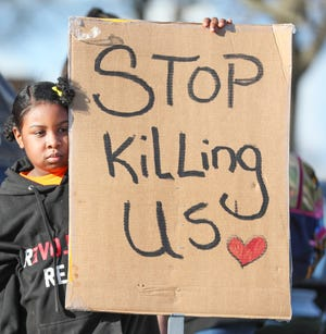 A tear rolls down the face of Afatiha Reynosa during a rally at Rose Park in Milwaukee on Monday in response to the death of Daunte Wright, a 20-year-old Black man, who was fatally shot by a Minnesota police officer on Sunday.