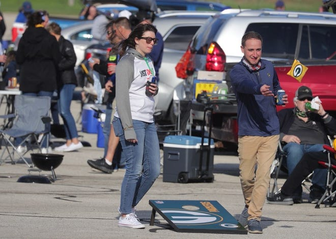 Fans tailgate before the Milwaukee Brewers game against the Chicago Cubs at American Family Field on Monday. This game marked the resumption of tailgating, which is permitted only at single vehicles for fans in the same seating pod. You also have to stay near your own vehicle.