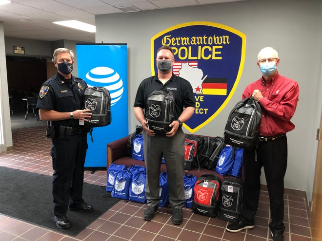 The Germantown Police Department received 20 bags with books for children ages 2-12. The bags are for the officers to read to children who are in a crisis. Pictured are, from left, Capt. Todd Grenier of the Germantown Police Department; Bill Posteluk of AT&T and Cory Erickson of Reach-A-Child.