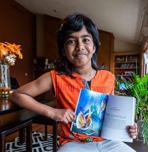 "Ten-year-old author Thaathwik Arsha Abhilash of Brookfield displays a favorite illustration from his recently published book, ""Dragon Summer."" The book was illustrated by Animesh Xavier."