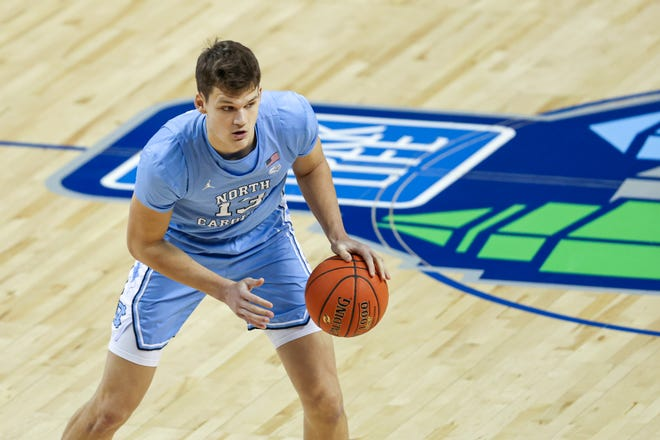 North Carolina forward Walker Kessler (13) looks to pass against Virginia Tech in the ACC Tournament on March 11, 2021, in Greensboro, N.C.