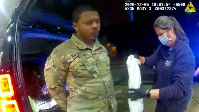 In this image made from police video in Windsor, Virginia, Army Lt. Caron Nazario is helped by an EMT after he was pepper-sprayed by police during a traffic stop.