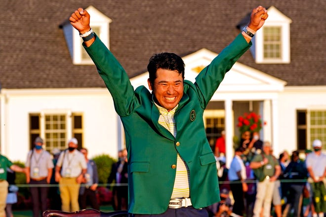 Hideki Matsuyama celebrates with his new green jacket on after winning the Masters.
